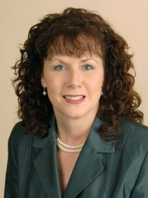 image of ruth mulnard wearing jacket and pearls in front of neutral backdrop