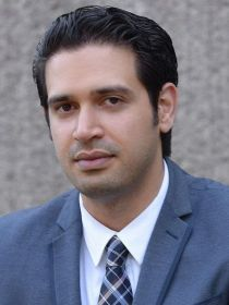 outdoor image of amir rahmani wearing white shirt, tie and gray jacket