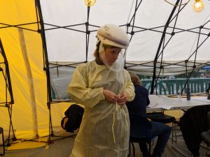 susanne phillips, dnp, puts on her ppe before testing patients for COVID-19