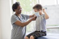 school nurse helping boy put on face mask for coronavirus
