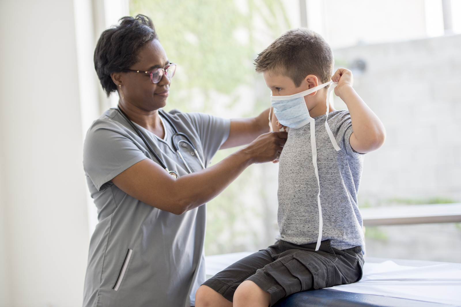 school nurse helping boy put on face mask for coronavirus
