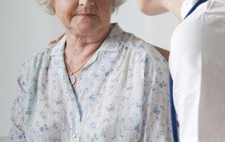 senior woman going through stress and trauma receiving care from a nurse