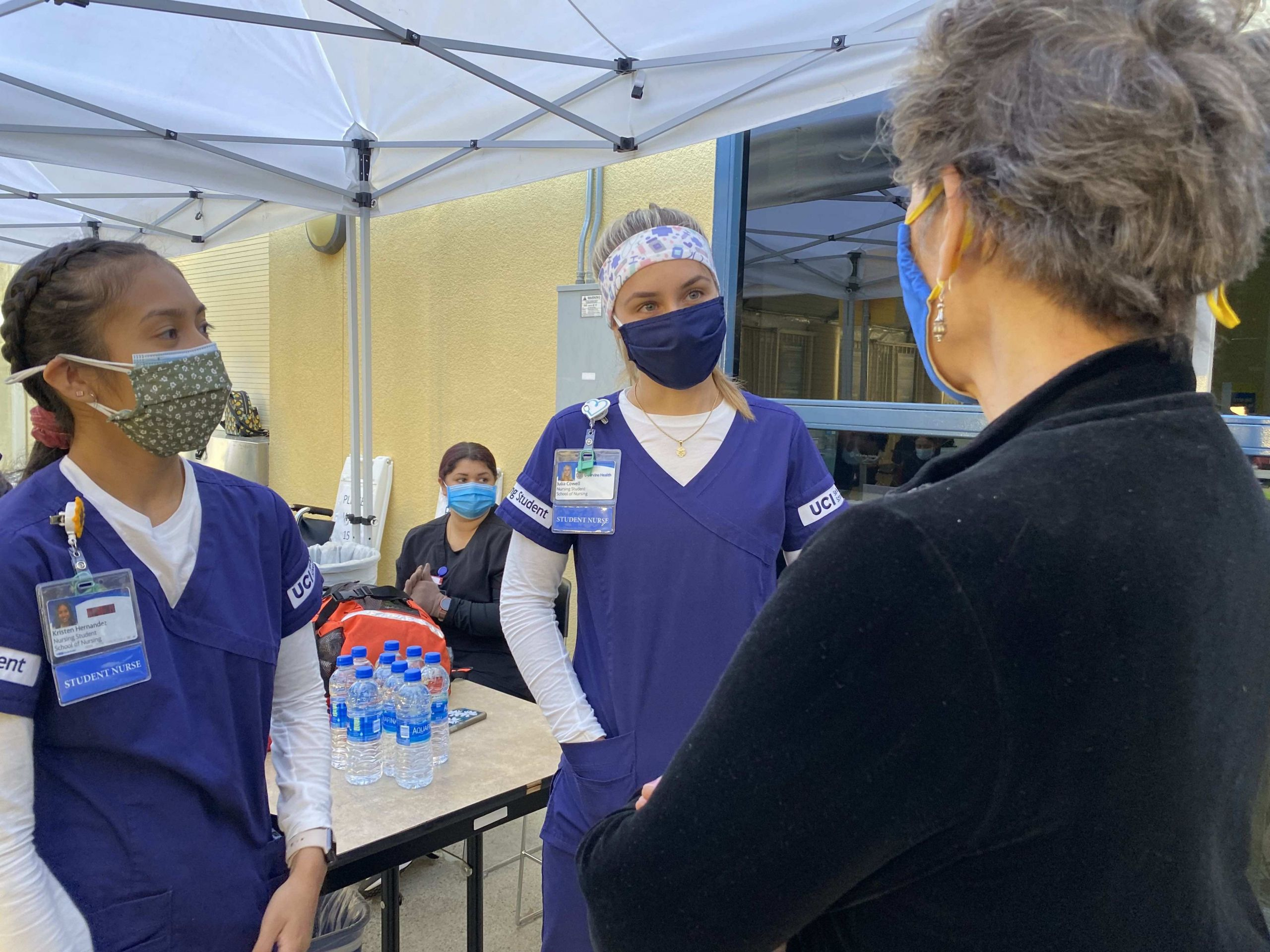 UCI School of Nursing Dean Adey Nyamathi talks to nursing students Julia Cowell (right) and Kristen Hernandez at the vaccination drive at the Bren Center.