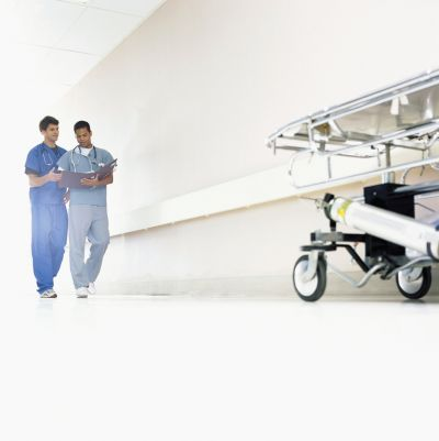 a nurse and doctor in scrubs walk down a hall while looking at medical chart