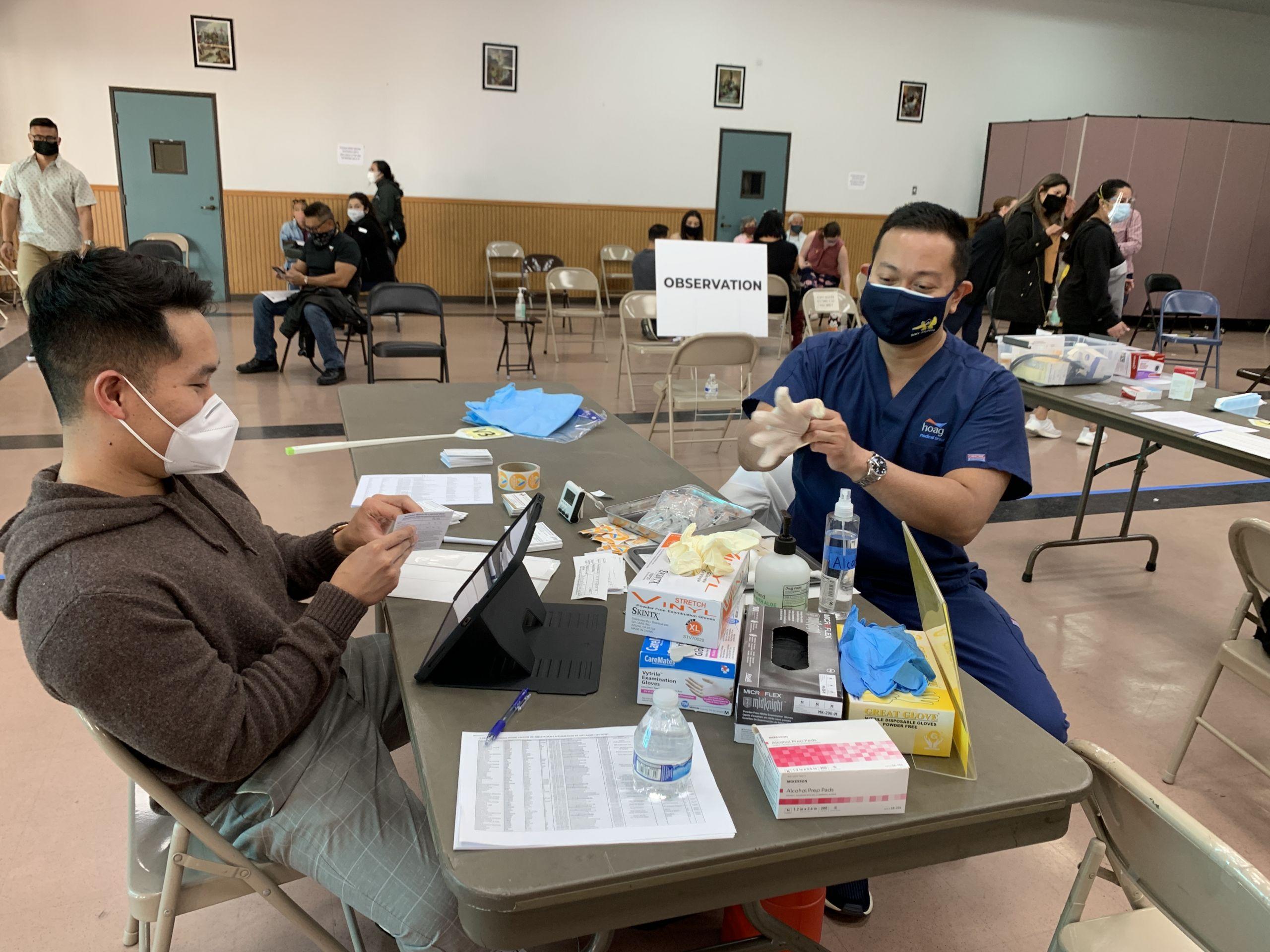 nurse practitioner john aldrich alejandro, right, preparing for a vaccination clinic