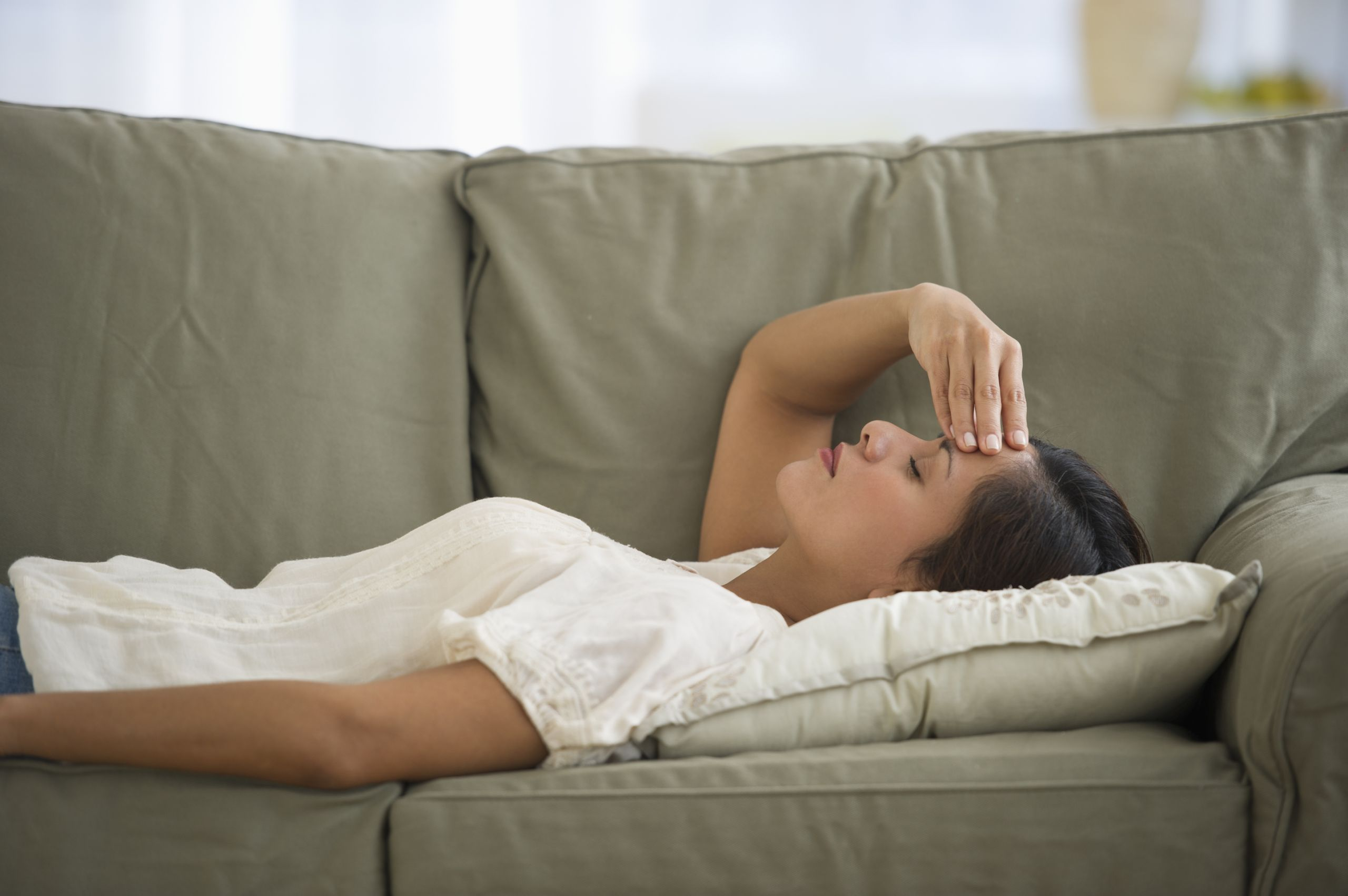 long covid sufferers are being invalidated and it is breeding patient mistrust; image of woman with headache laying on couch