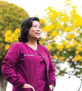 photo of uc irvine health oncology nurse van pham in burgundy uniform with trees in background