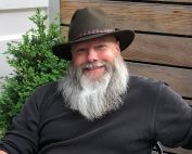 uci department of logic and philosophy professor kyle stanford with white beard, brown shirt, brown hat, smiling